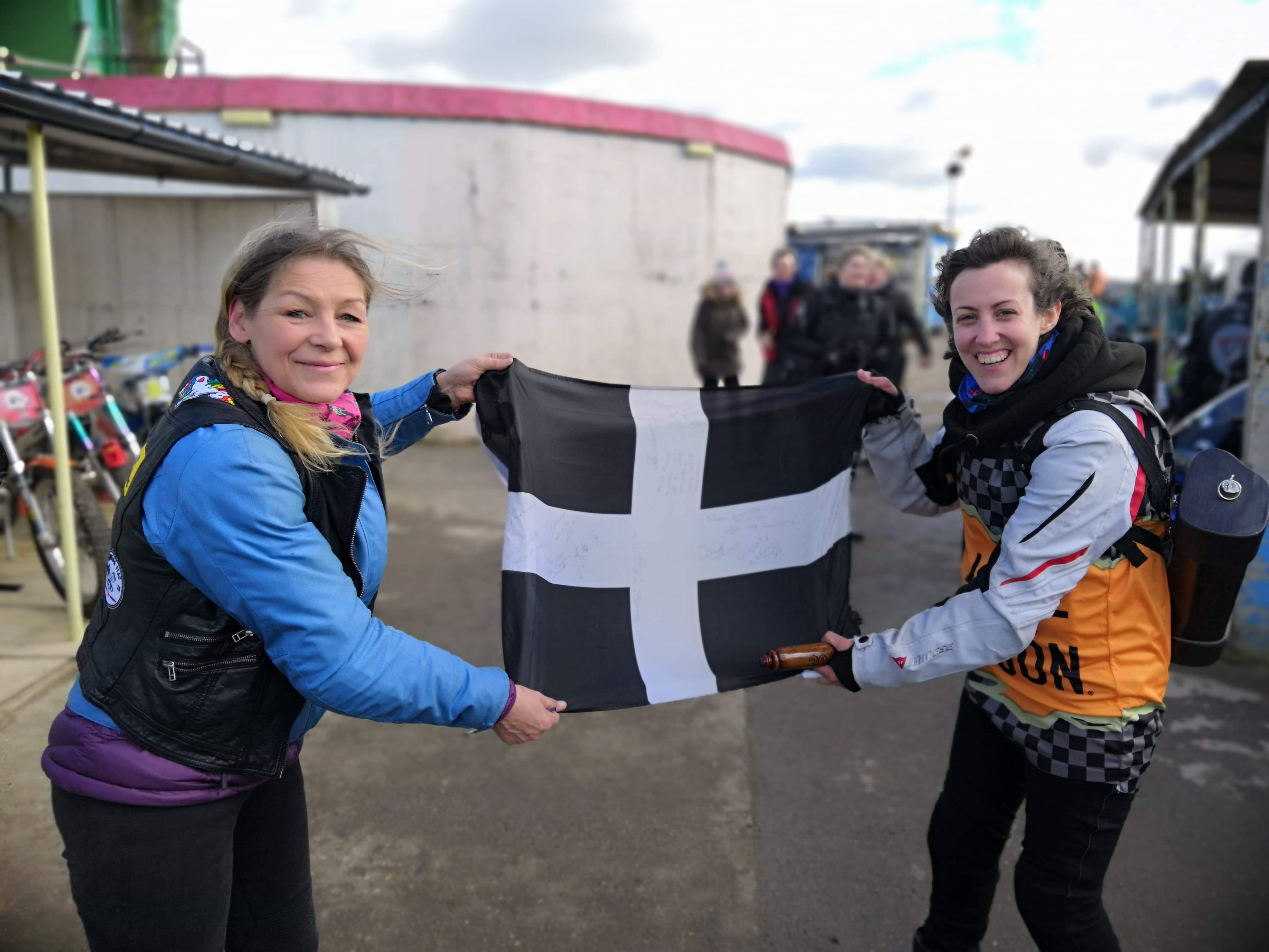 two lady motorcyclists holder a Cornish Flag